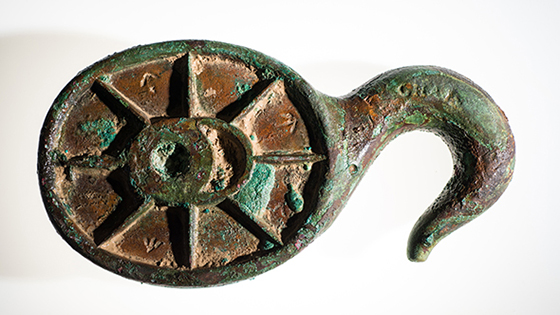 "Among the artifacts recovered are a number of pieces of Erebus' equipment and rigging, including fragments of the ship's wheel, illuminators that allowed light into the lower decks, and rigging blocks and belaying pins to handle the masses of hemp ropes on such sailing vessels. This solid copper-alloy hook block, marked with several British broad arrows and ""6 1/4"" referring to its size, may have been used to lower one of the ship's smaller boats or formed parts of its standard rigging. (Parks Canada)"
