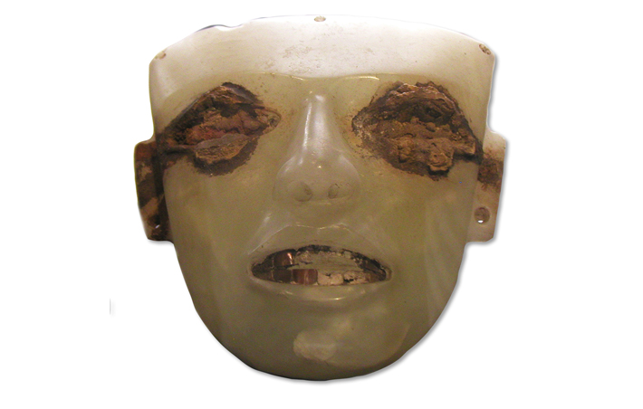 "A weathered travertine face has inlaid shell teeth and iron oxide staining around the eyes, suggesting they were once inlaid with iron pyrite, or ""fool's gold."""