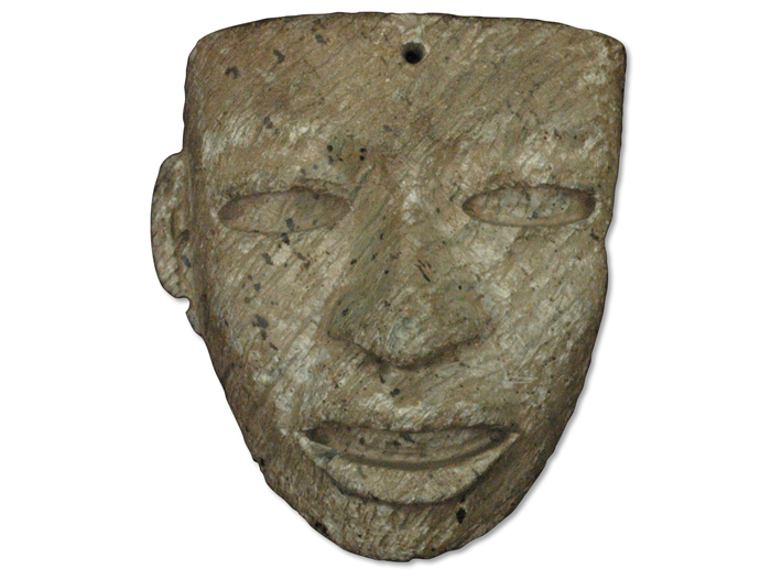 This stone face fashioned from gray-green serpentinite has a hole drilled through its temple that may have been used to attach it to a larger display.