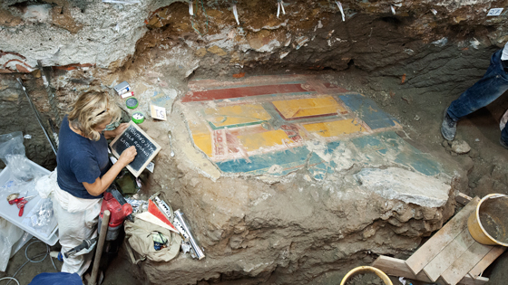 Archaeologist Luciana Jacobelli studies a large collapsed fresco fragment. The visible side of the painting probably decorated the wall of an as-yet unidentified room, while the opposite side, now embedded in the ground, was featured in the triclinium. (Marco Merola)