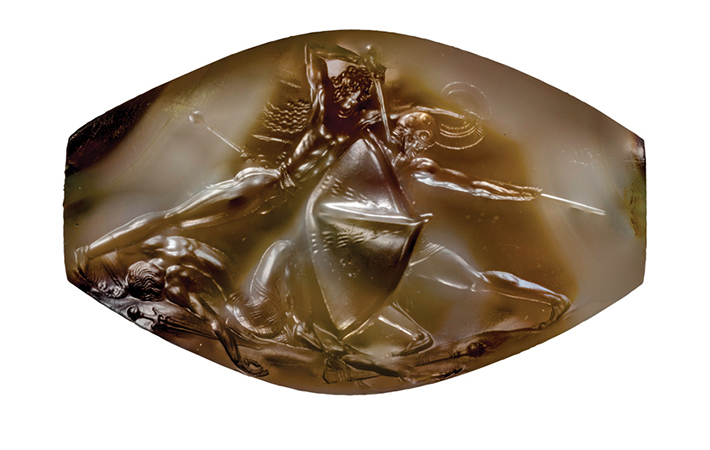 The Pylos Combat Agate is one of 50 decorated seal stones to have been found in the Griffin Warrior's tomb. It measures only 1.4 inches wide and depicts a leaping warrior stabbing an armored enemy in the neck. Another foe lies dead at his feet.