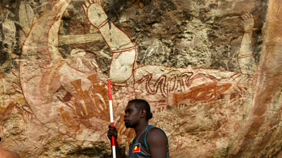 Patrick Lamilami, youngest son of Ronald, the traditional owner of the land where both Djulirri and Malarrak reside, now sometimes works as a guide to the area's rock art sites. Here he stands before the central panel at Malarrak, which is dominated by a large painting of a crocodile. There is a similar depiction at Djulirri. The crocodiles may have been painted as markers of culture in a time of great change—when outsiders first arrived.