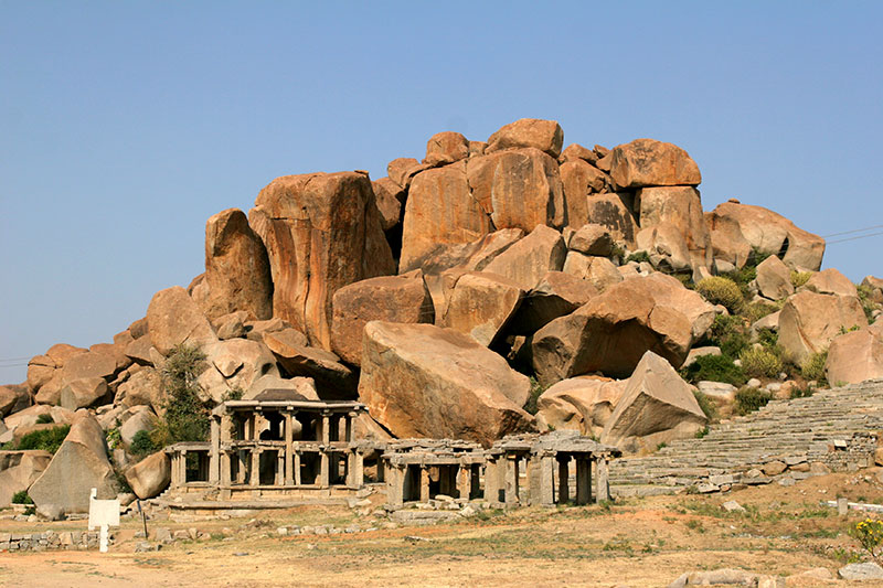 Colonnade structures at the far end of Hampi Bazaar mark the beginning of the trail to the top of Matanga Hill, set against the granite boulders that make up the surrounding landscape.